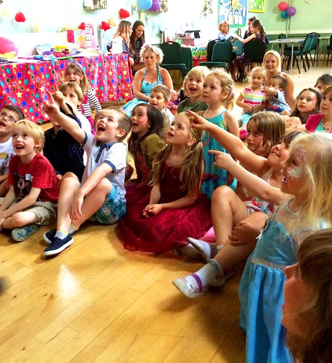 Children's entertainer Andy Hiccup entertaining a crowd of children in a village hall