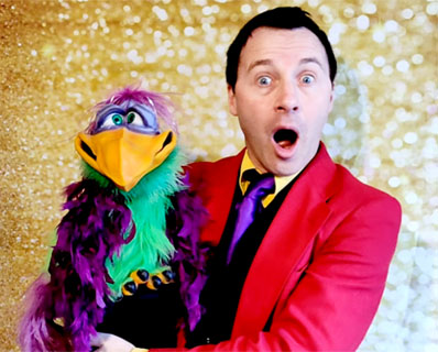 A Surrey children's party entertainer, wide mouthed and surprised, holds an ugly puppet bird.