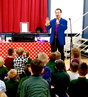 Children's entertainer Andy Hiccup entertaining a crowd of children with some milk-based magic