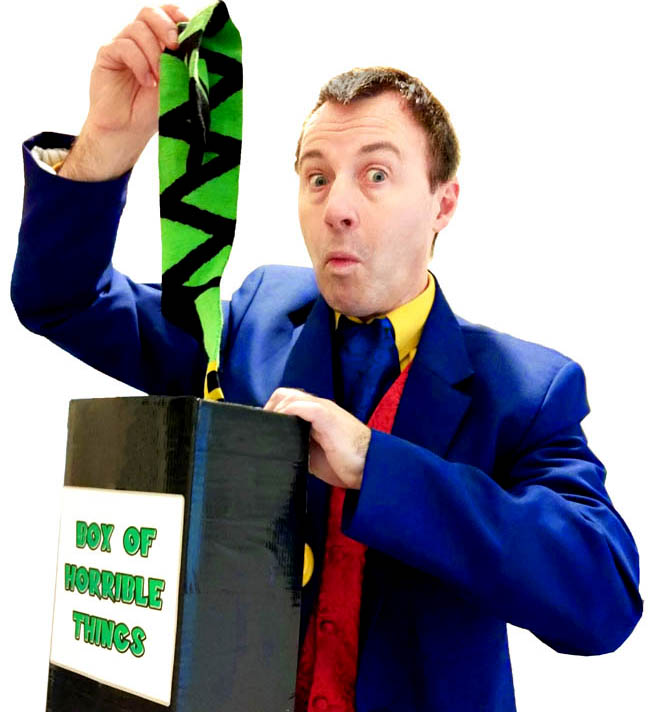 Magician Andy Hiccup pulls a long green sock out of his Box of Horrible Things. He pulls a face.